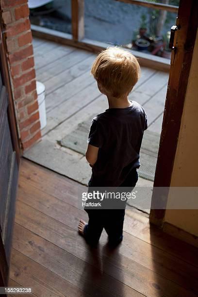A young boy standing in an open doorway