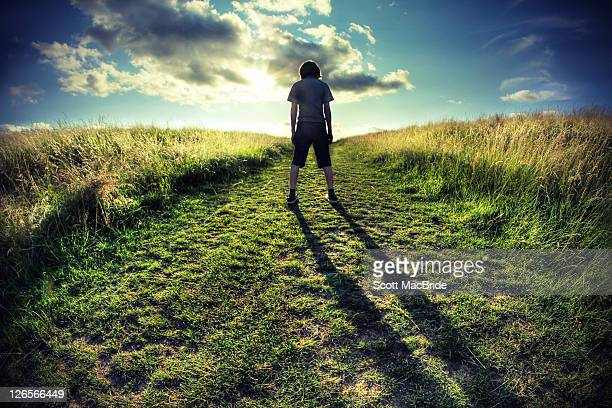 young boy standing in field with shadow on ground - scott macbride stock pictures, royalty-free photos & images