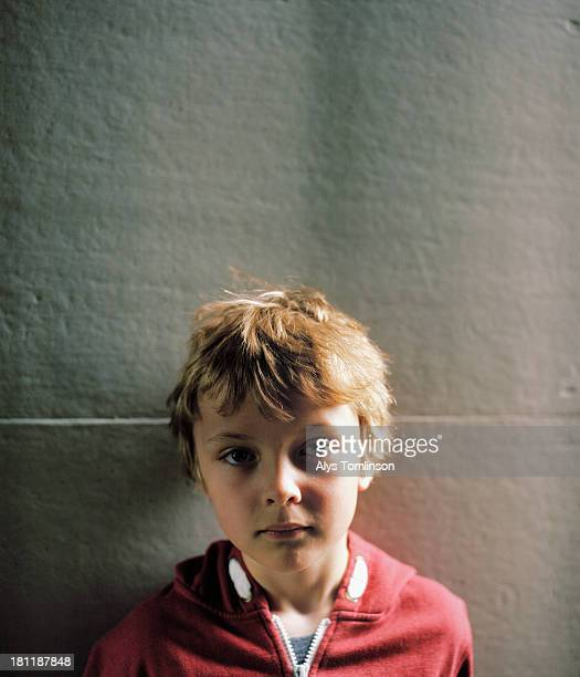 Young boy standing in front of a wall