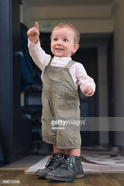 Young boy standing in his father's shoes and pointing up