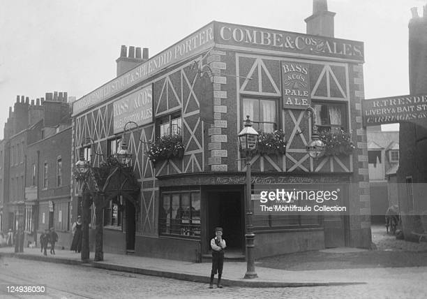 Young boy standing in the road outside the Angel Inn, Highgate, with livery yard for horse and carriages to the righthand side; London, England 1895.
