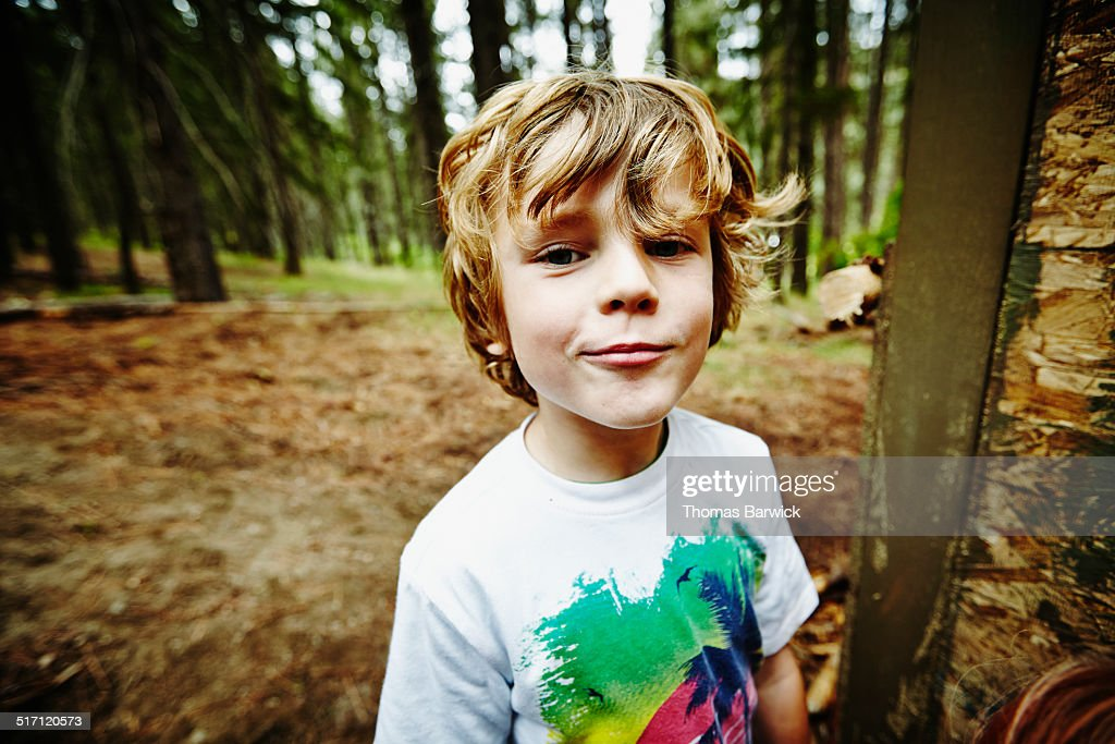 Young boy standing in the woods at camp : Stock Photo