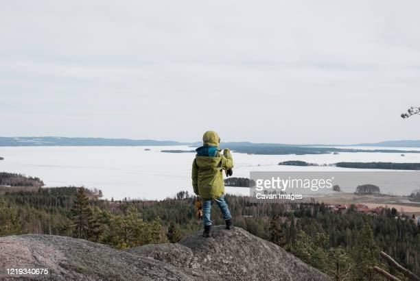 young boy standing on a rock looking out at the view of the ocean - rock baby sleep stock pictures, royalty-free photos & images