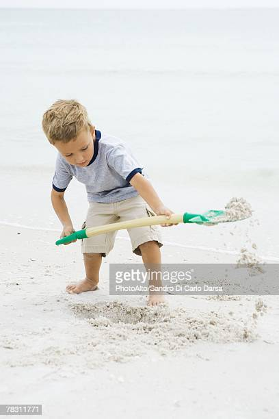 Young boy standing on beach, digging in sand with shovel, looking down