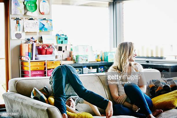 young boy standing on head on couch next to mother - naughty america stock photos and pictures