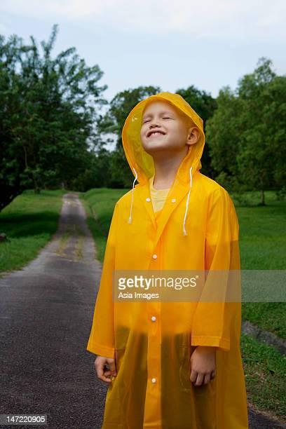 young boy standing on road in rain coat