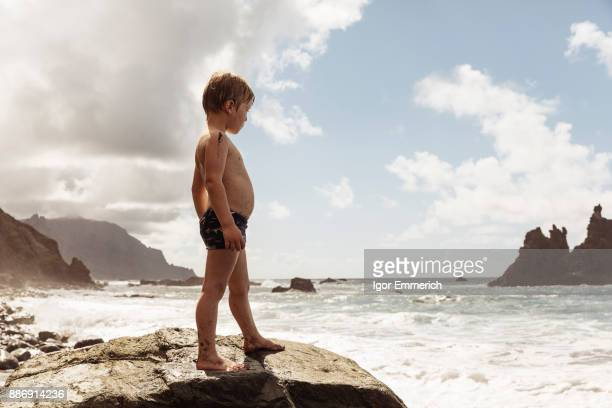Young boy standing on rock, looking at view, Santa Cruz de Tenerife, Canary Islands, Spain, Europe
