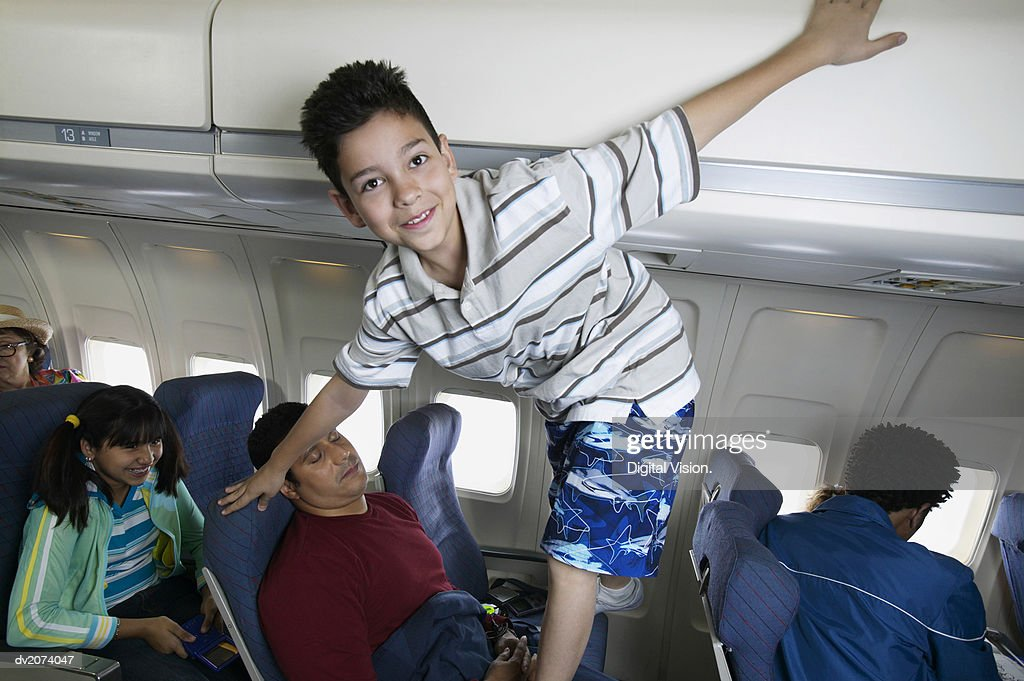 Young Boy Standing on Seating During a Aeroplane Flight : Stock Photo