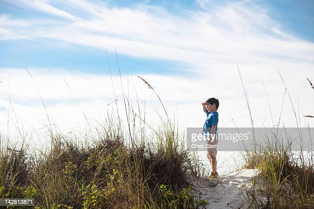 Young Boy standing on top of a Beach Dune