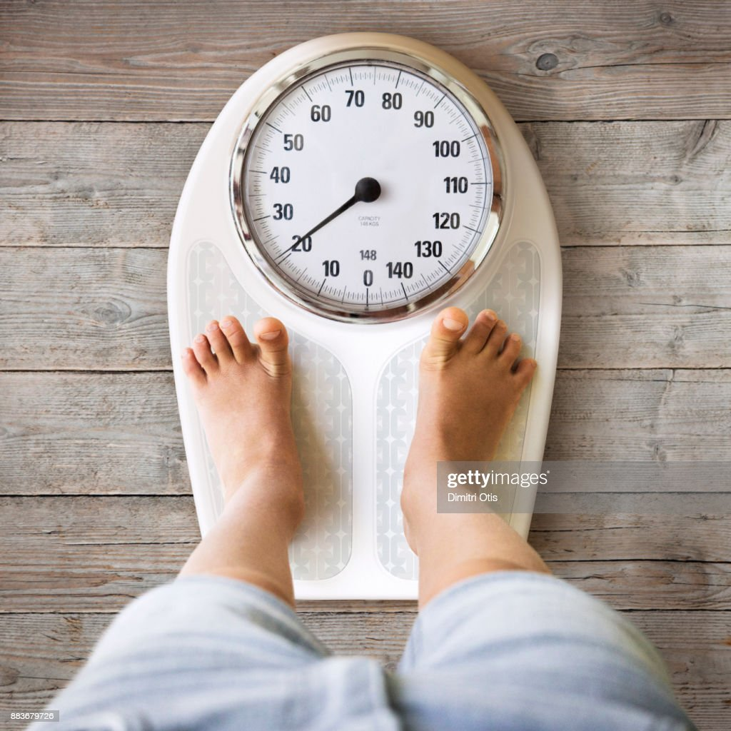 Young boy standing on weight scales : Stock-Foto