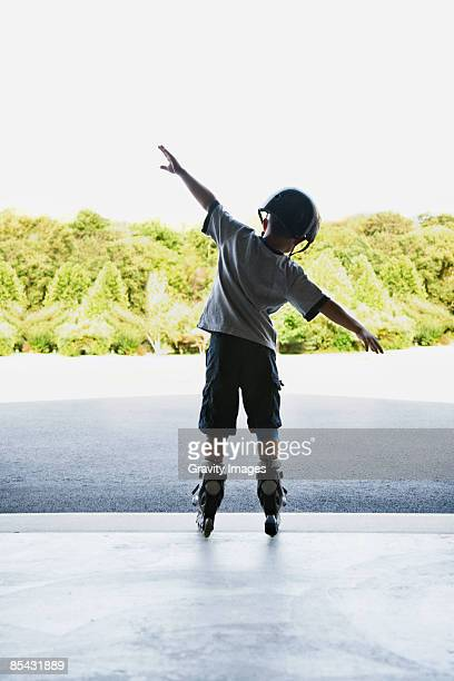 Young boy standing with arms out on roller blades