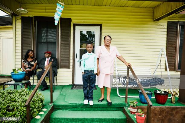 young boy standing with grandmother on front porch of home - texas stock pictures, royalty-free photos & images
