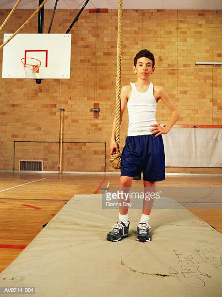 Young boy (12-14) standing with rope in gym, portrait