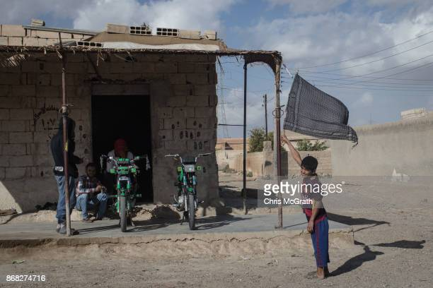 A young boy stands holding a black scarf made into a flag on a street in the western neighborhood of Jazrah on the outskirts of Raqqa on October 30...