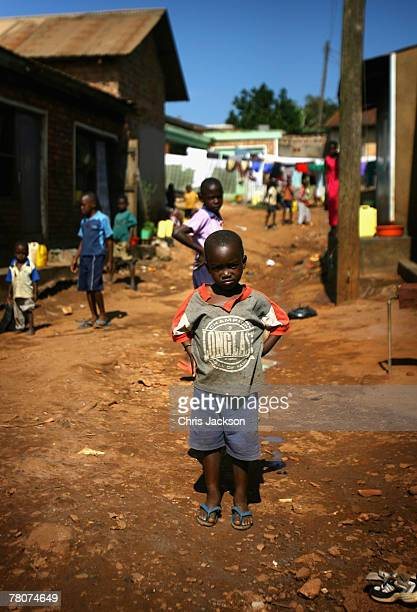 A young boy stands in a dusty street before the arrival of Prince Charles Prince of Wales in Kawempe Slum on November 23 2007 in Kampala Uganda Many...