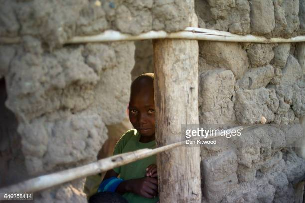 A young boy stands in a mud hut at the Kerwa Receiving Centre after being brought from the South Sudanese border on February 23 2017 in Kuluba Uganda...