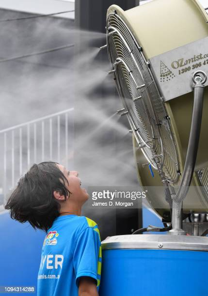 Young boy stands in front of a water fan to keep cool during day two of the 2019 Australian Open at Melbourne Park on January 15, 2019 in Melbourne,...