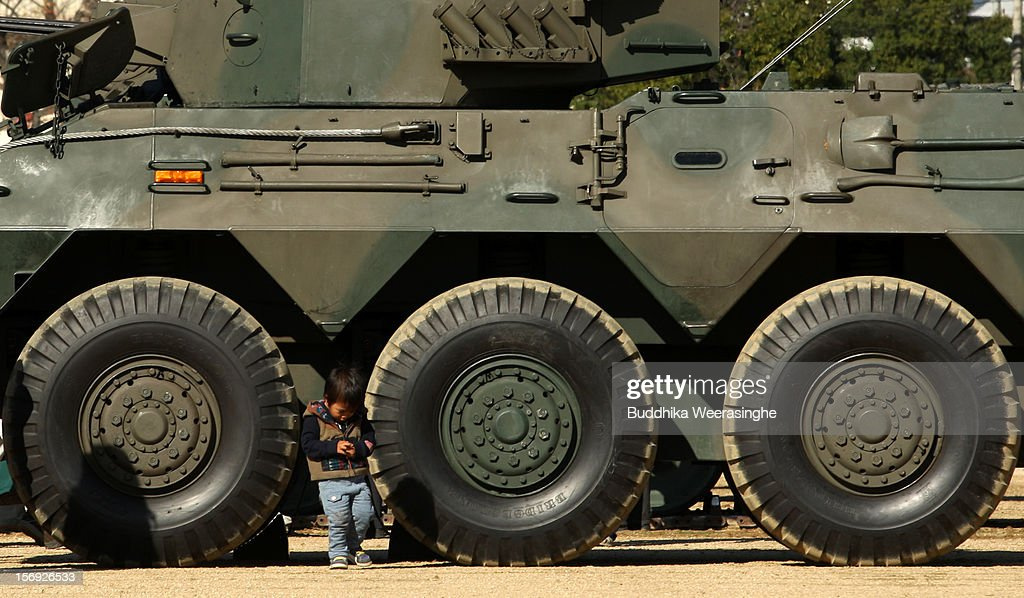 A young boy stands in front of an armed vehicle during the annual Japan Ground Self-Defense Force (JGSDF) military demonstration on November 25, 2012 in Himeji, Japan. The military exhibition and demonstration marks the 61-year anniversary of the Japan Ground Self-Defense Force based in Himeji.