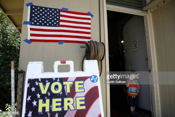 A young boy stands in the doorway of a polling station at a Ross Valley fire station on June 5 2018 in San Anselmo California California voters are...