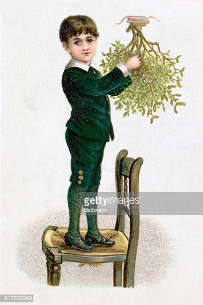 A young boy stands on a chair in order to mount a sprig of mistletoe onto the ceiling in preparation for the Christmas season Undated color...