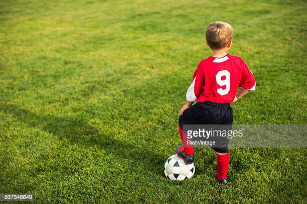 Young Boy stands on Grass Soccer Field