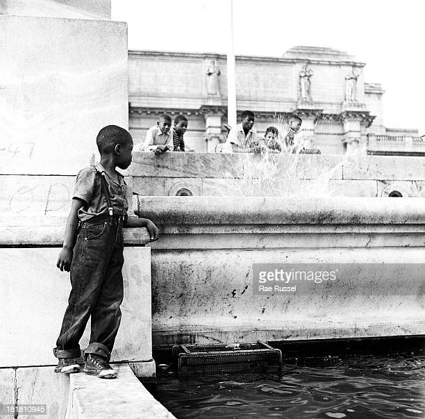 Young boy stands on the edge of a fountain as others watch from above him, Washington DC, 1948.