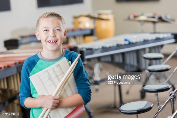 young boy stands proudly in his school music room - percussion instrument stock photos and pictures