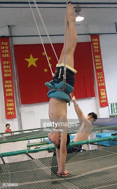A young boy stands upside down as he practises diving movements with the help of a coach at a diving school on May 10 2005 in Chengdu of Sichuan...