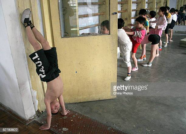 A young boy stands upside down as he practises diving movements with his teammates at a diving school on May 10 2005 in Chengdu of Sichuan Province...