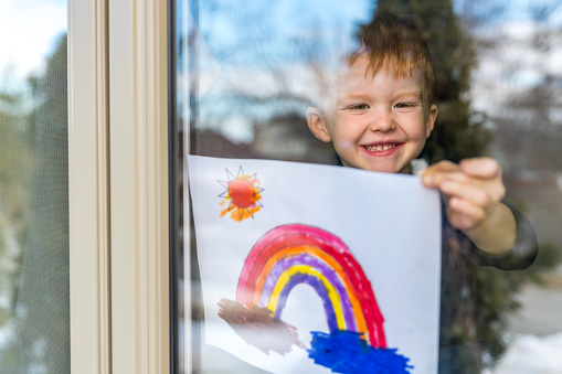 Young Boy sticking his drawing on home window during the Covid-19 crisis 1214595977
