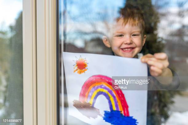 young boy sticking his drawing on home window during the covid-19 crisis - rainbow stock pictures, royalty-free photos & images