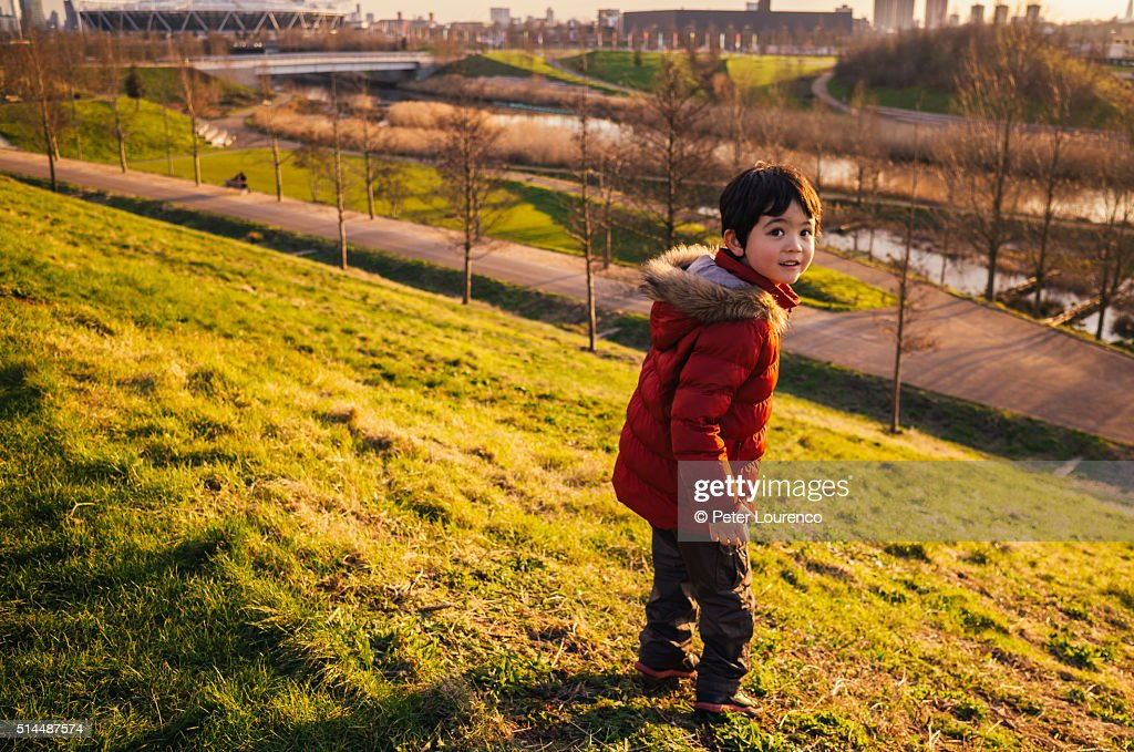Young boy stood at the top of a grass hill : Stock-Foto