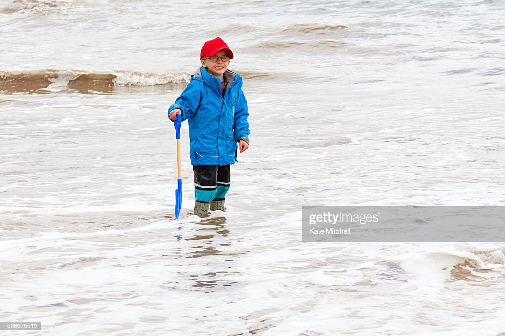 Young boy stood in the sea fully clothed : Stock Photo