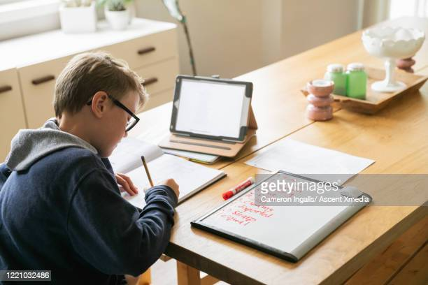 young boy studies at home with a digital tablet and school books. - cameron young - fotografias e filmes do acervo