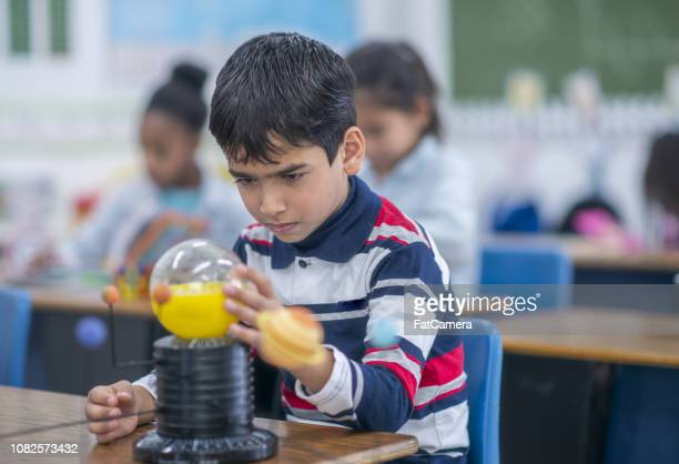 Young boy studying science in class