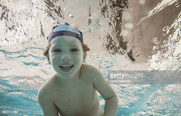 A young boy swimming underwater in a pool