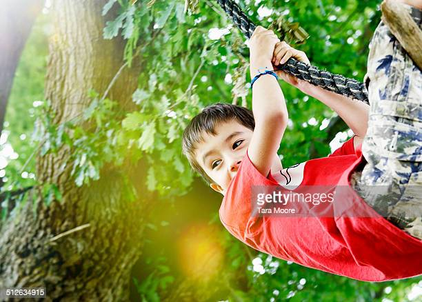 young boy swing in park on rope