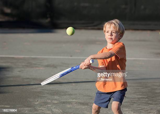Young boy swinging a tennis racket at a tennis ball