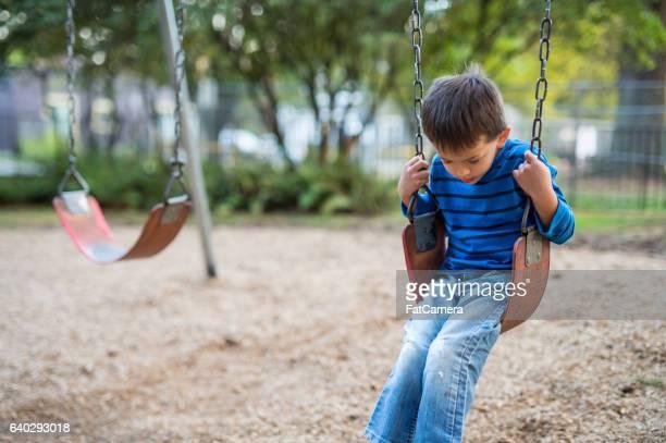 young boy swinging by himself on playground - tristeza fotografías e imágenes de stock