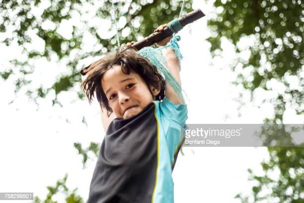 young boy swinging on home-made swing in tree, low angle view - innocence stock pictures, royalty-free photos & images