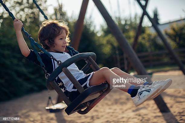 young boy swinging - only boys stock pictures, royalty-free photos & images