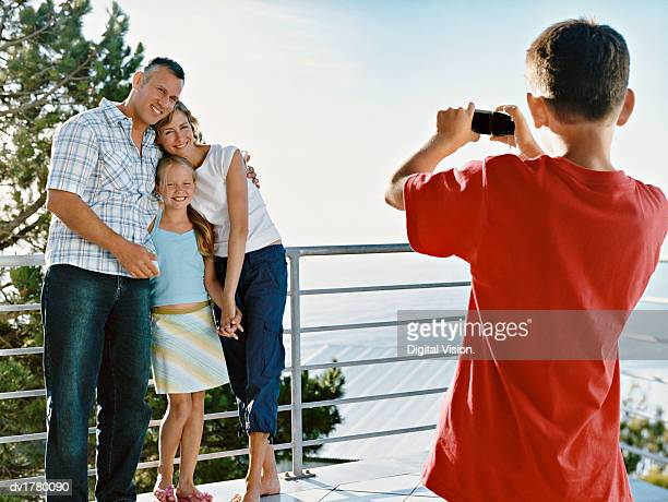 young boy takes a picture of his parents and sister, standing with their arms around each other on a balcony - travel14 stock pictures, royalty-free photos & images