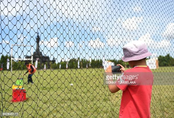 A young boy takes a picture with a mobile phone through the safety fence prior to the start of the FAI Drone Racing World Cup event in Denpasar on...