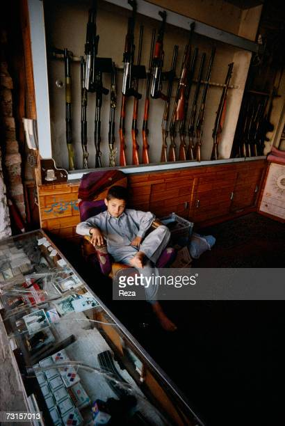 A young boy takes care of the family gun room in the Pahtun tribal zone on July 2004 in Sakha Kot Pakistan
