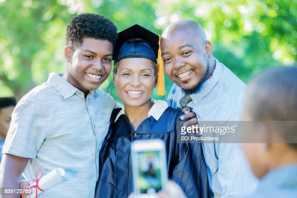young boy takes picture of family after mom's graduation ceremony - beautiful wife pics stock pictures, royalty-free photos & images