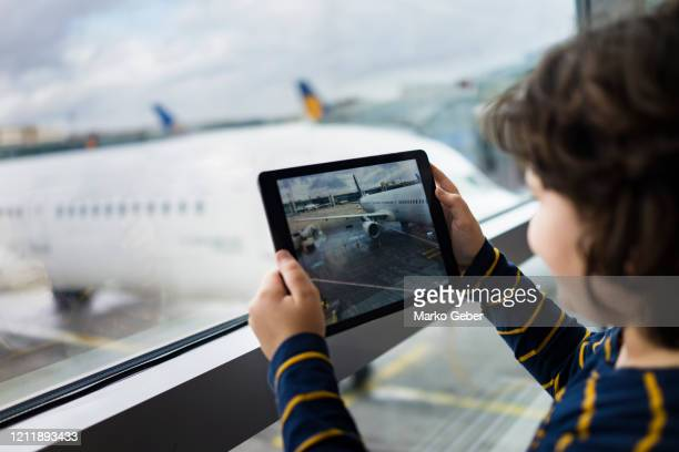 young boy taking a picture of a plane - kid in airport stock-fotos und bilder