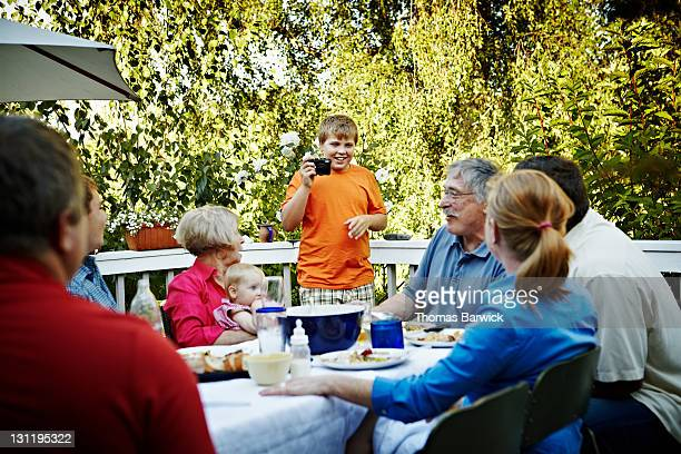 Young boy taking digital photo of family at table