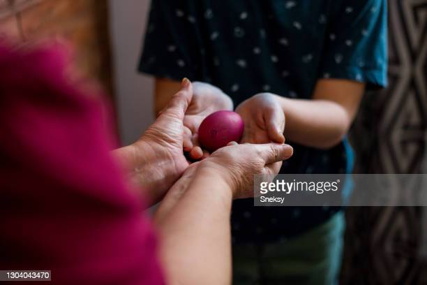 young boy taking easter egg that his granny is giving him. selective focus. - orthodox easter stock pictures, royalty-free photos & images