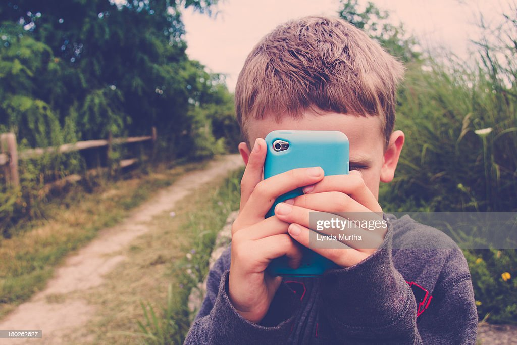Young boy, blond/brown short hair, with mobile device raised in front of face, taking picture with camera with turquoise blue cover. Grey casual sweatshirt.