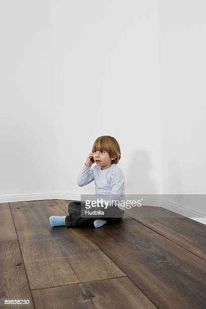 A young boy talking on a cell phone